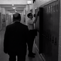 A teacher accosts a student putting things in his locker.